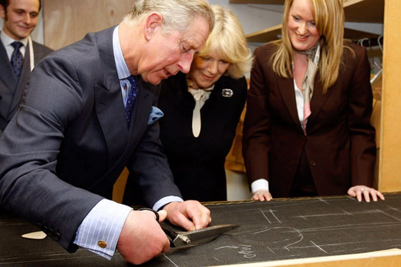 The Prince of Wales tries his hand at cutting a wool fabric for a suit
