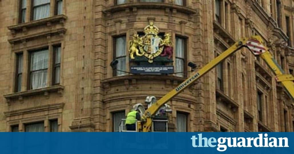 A man removes the Royal Warrants from Harrods façade
