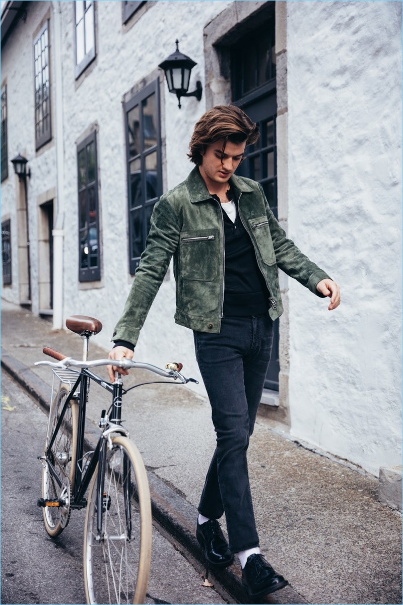 Actor Joe Keery wears a Tom Ford sweater and suede jacket with Acne Studios jeans. Keery also rocks J.Crew dress shoes.