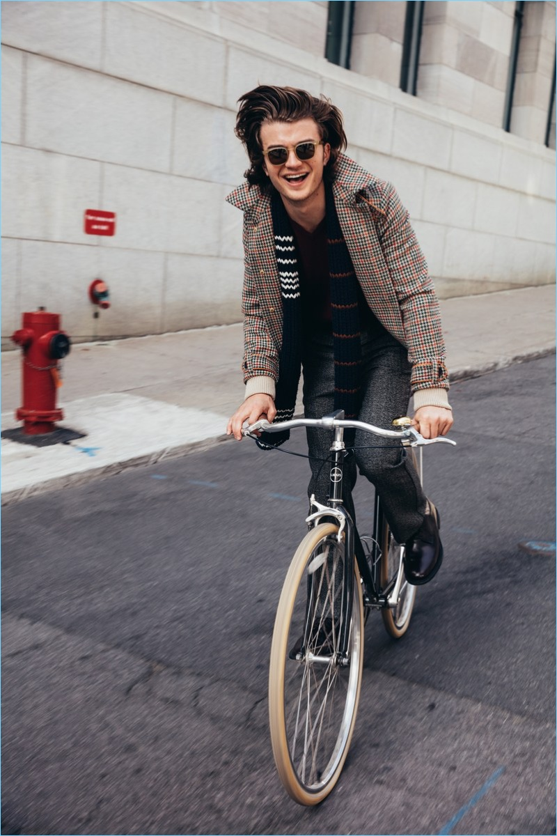 Taking a bike ride, Joe Keery wears a Prada jacket, sweater, scarf, and trousers. He accessorizes with Church's shoes and Steven Alan sunglasses.