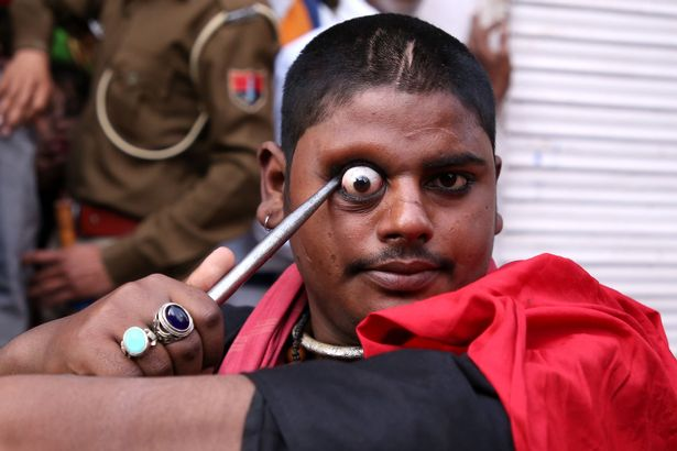 Worshipers use knives to expose their eyes at religious festival